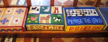 Handsewn kneelers in Wessington Church showing animals, tractors and music notes
